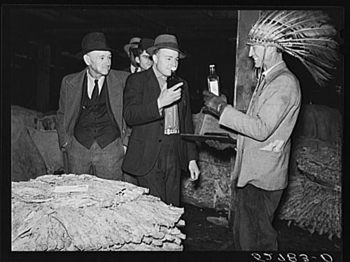 Marion Post Wolcott 1939 Farmers listening to sales talk of patent medicine vendor in warehouse during tobacco auctions. Durham, North Carolina.