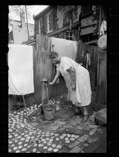 Carl Mydans Outside water supply Washington DC Only source of water supply winter and summer for many houses in slum areas In some places drainage is so poor that surplus water backs up in huge puddles 1935