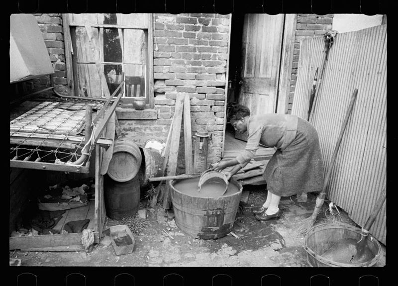 Carl Mydans Slum backyard water supply Washington DC Backyard typical to a group of houses very close to the House office building showing only available water supply 1935