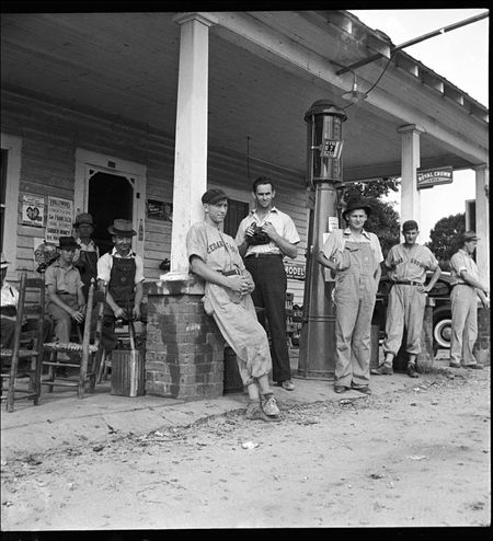 Dorothea Lange Fourth of July near Chapel Hill North Carolina Rural filling stations become community centers and loafing grounds men in the baseball suits are local team which will play game nearby They are the Cedargrove Team 1