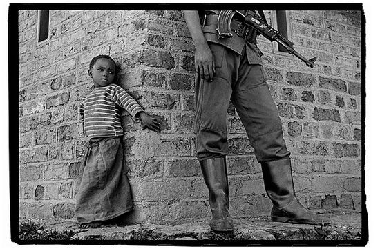 Nachtwey A young girl warily eyes a guerrilla fighter in the Lubero district Congo