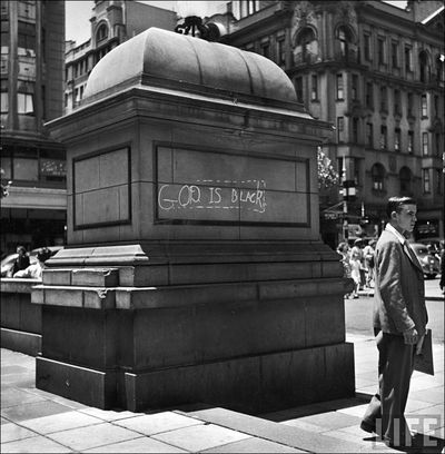 23 Bourke White Young white man standing next to statue w GOD IS BLACK chalked on the base outside city hall 1950